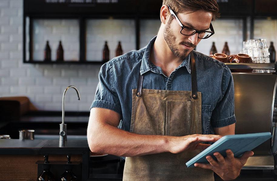 Man in coffee shop holding an iPad